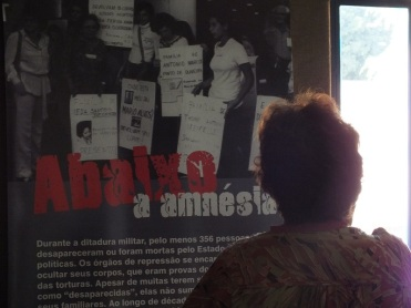 """Amparo Almeida Araújo vor einem Plakat der Ausstelung """"Amnestie und Demokratie"""" mit dem Spruch""""Nieder mit der Amnestie"""" // C: Sara Fremberg"""