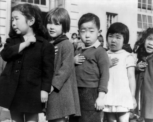 First-graders, some of Japanese ancestry, at the Weill public school, San Francisco, Calif., pledging allegiance to the United States flag. The evacuees of Japanese ancestry will be housed in War relocation authority centers for the duration of the war . (Photo by Dorothea Lange).