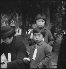 Hayward, California, May 8, 1942. Two children of the Mochida family who, with their parents, are awaiting evacuation bus. The youngster on the right holds a sandwich given her by one of a group of women who were present from a local church. The family unit is kept intact during evacuation and at War Relocation Authority centers where evacuees of Japanese ancestry will be housed for the duration. (Photo by Dorothea Lange).